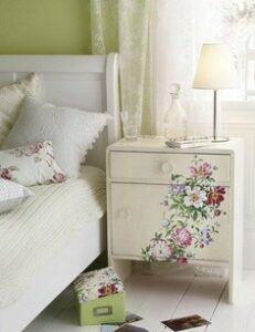 Painted nightstand in a shabby chic bedroom with lacy curtains.