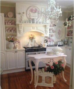 A Shabby Chic kitchen with pink table being used as an island.
