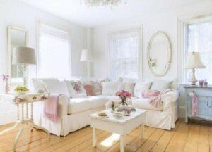 Shabby chic living room with sectional sofa and pink pillows.