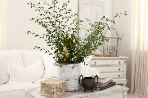 An all white shabby chic living room with greenery on the coffee table.